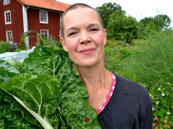 Sara Bäckmo i Skillnadens Trädgård med ett stort fång mangold.