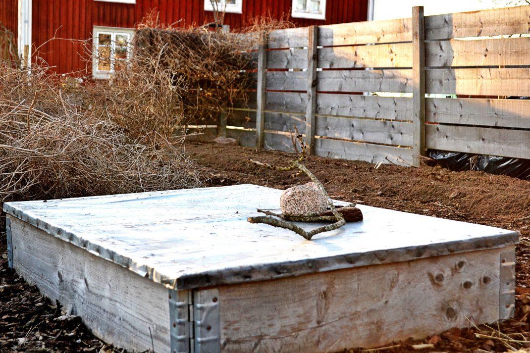 En pallkrage med lock på står i köksträdgården.