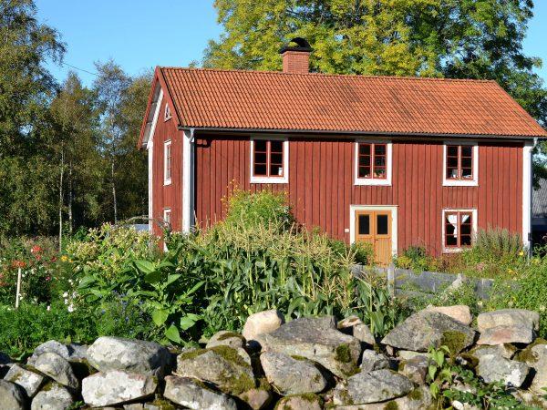 Huset Skillnadens med en stenmur och köksträdgård i förgrunden.
