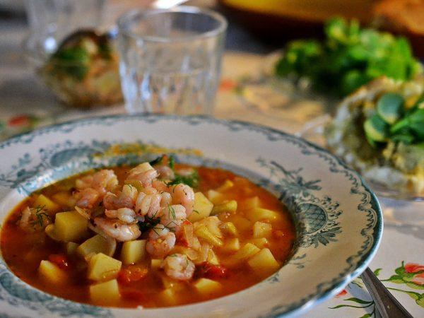 Middagsbord med soppa i tallriken och smörgås bredvid.