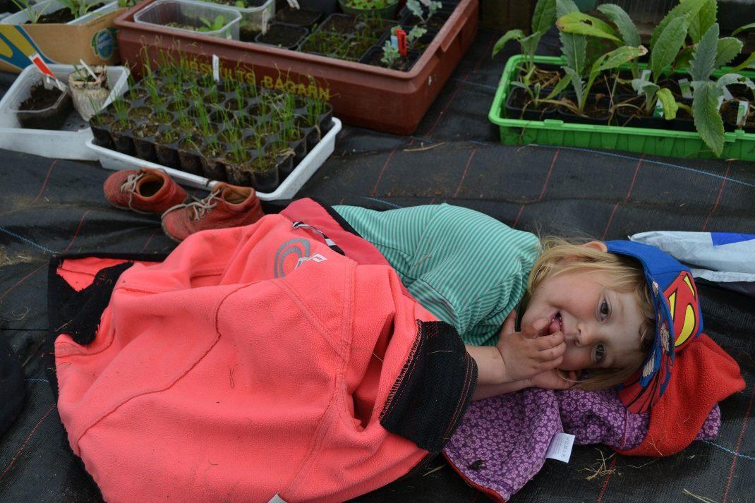 Ett barn har bäddat ner sig själv under en jacka och parkerat skorna bredvid.