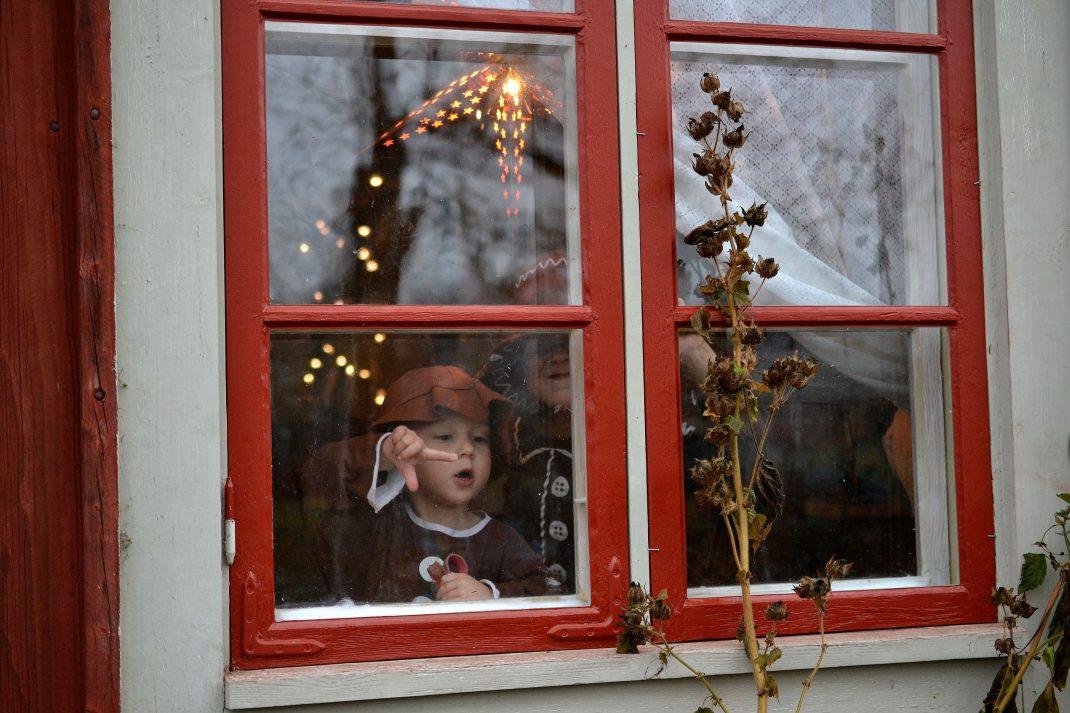 Barn i pepparkaksdräkter i ett juligt fönster.