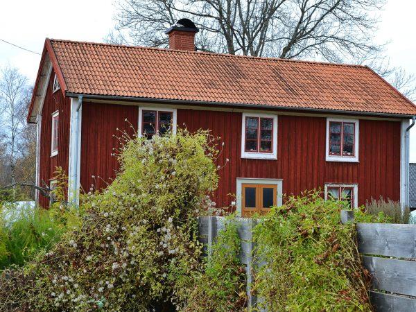 Ett vackert rött hus i Skillnadens Trädgård.