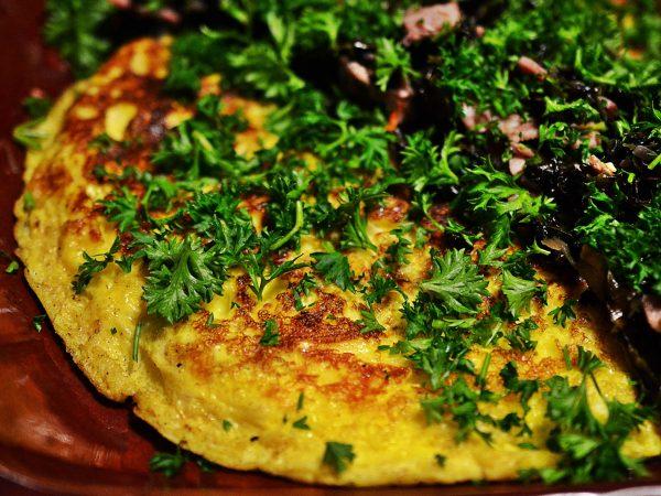 Omelett på ett fat tillsammans med bräserad kål och persilja.