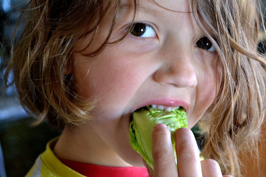 En pojke med långt hår äter sallat.