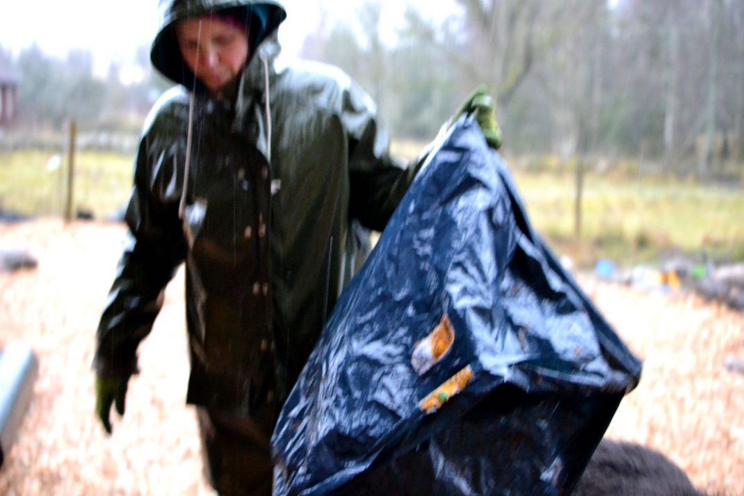 Sara i regnkläder med en svart sopsäck i handen.