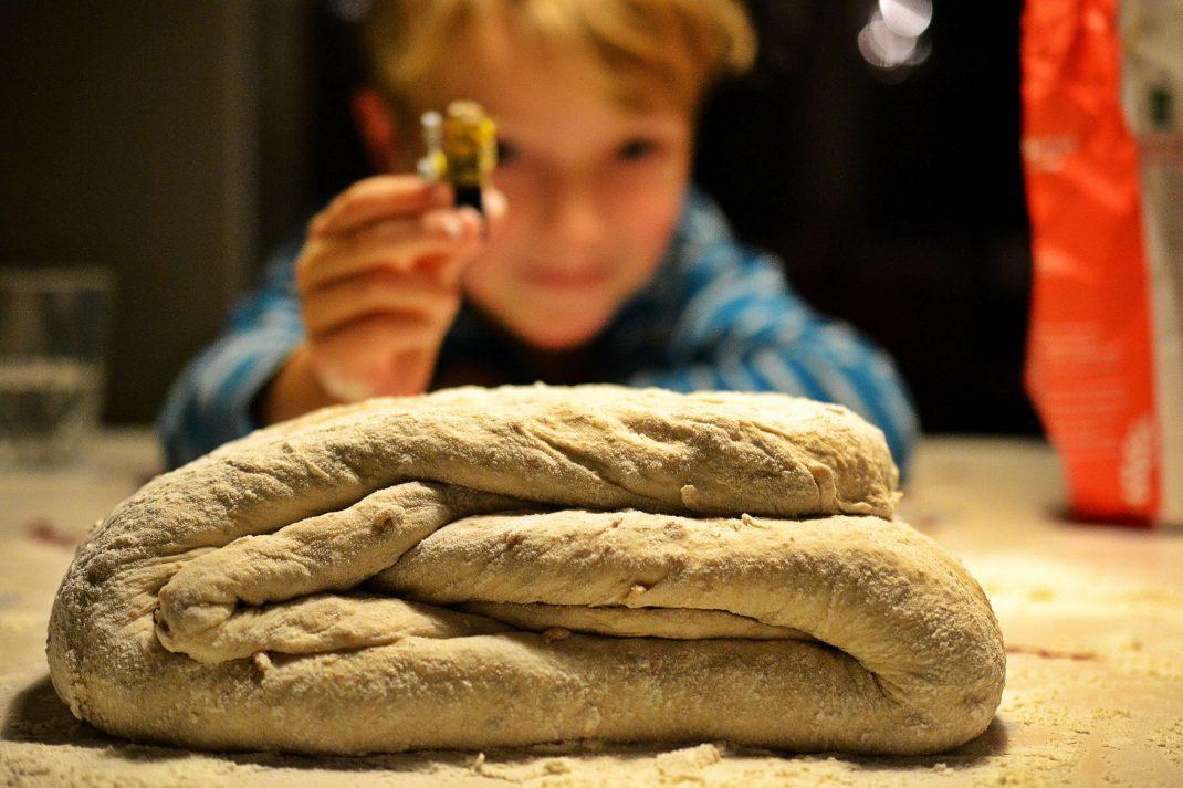 En bröddeg ligger vikt på mjölat bord med ett barn som håller en legogubbe i bakgrunden.