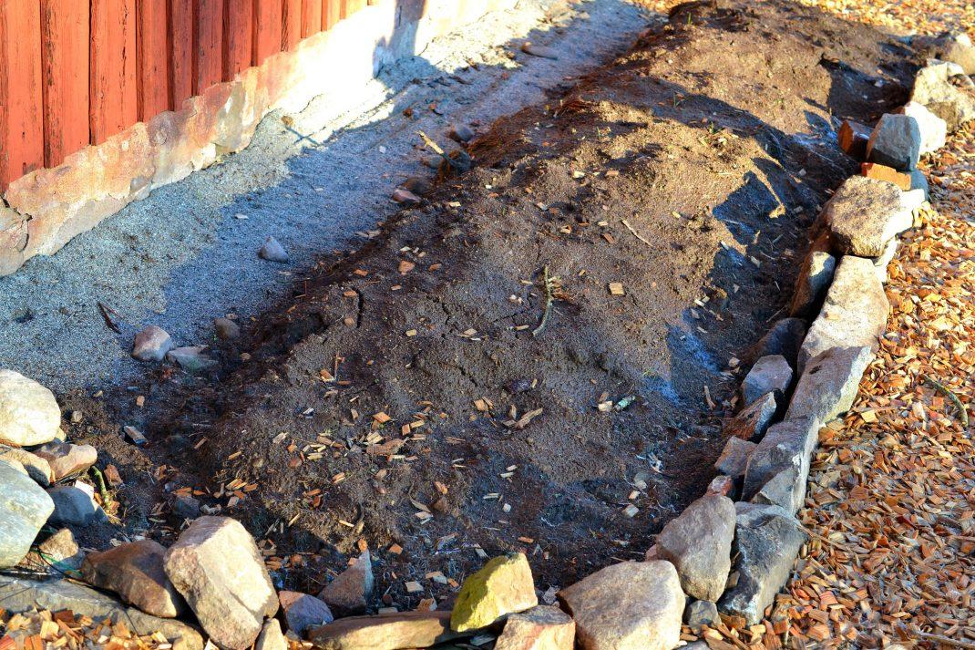 En odlingsbädd längs husgavel i söderläge, inramad av kant av sten.