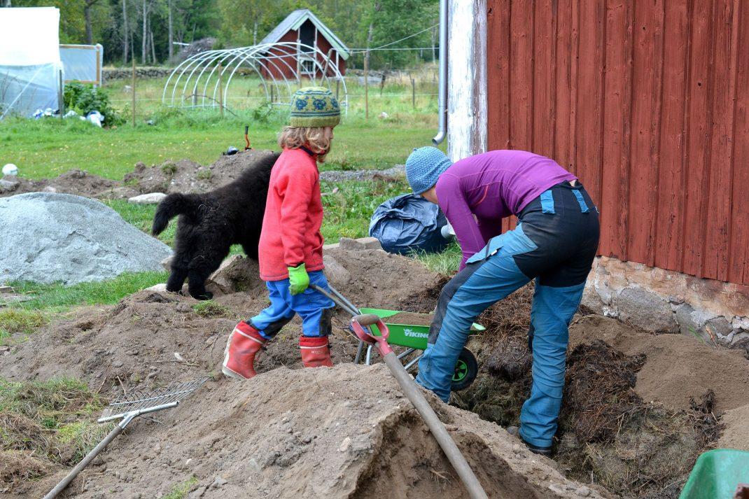 Jag och Otto jobbar tillsammans med att lassa jord på bädden.