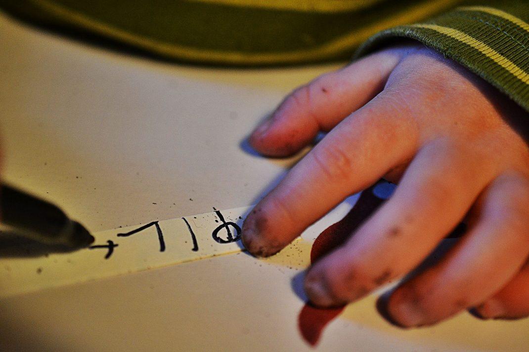 Barn skriver bokstäver på en plantetikett.
