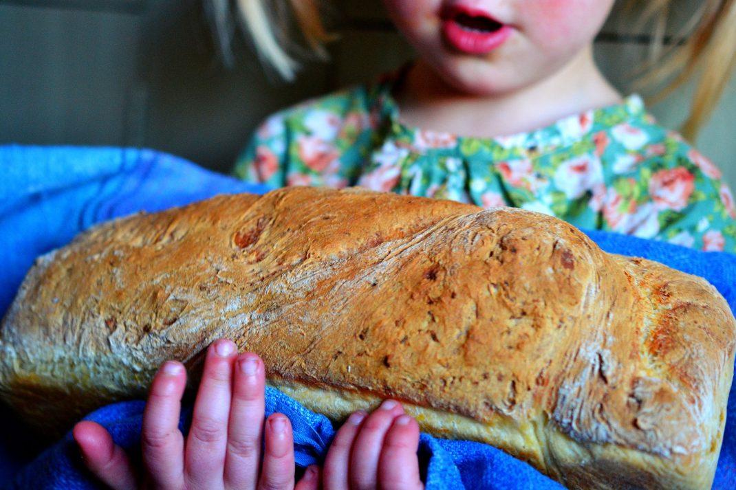 En liten tjej håller ett stort formbröd i famnen.
