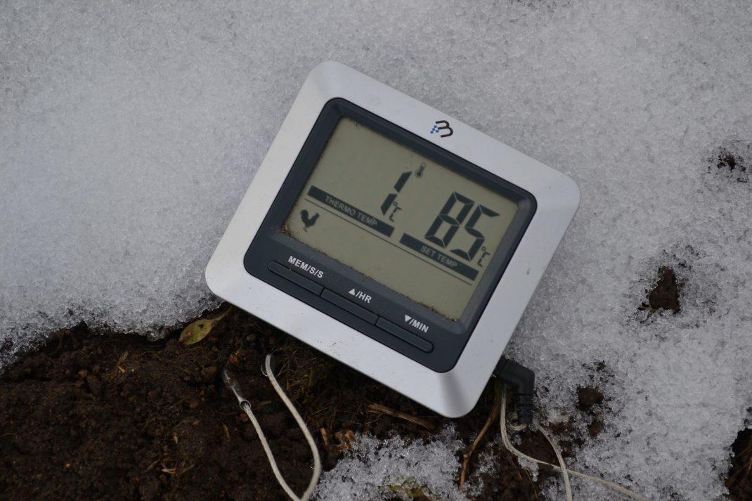 En termometer nerstucken i snötäckt odlingsbädd.