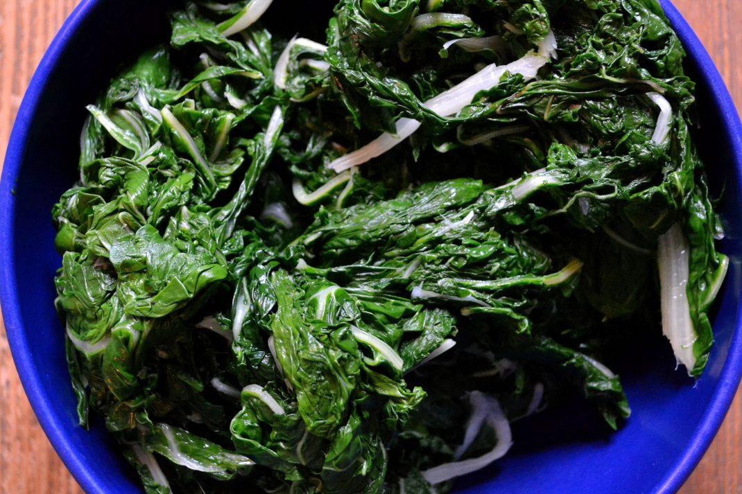 Gröna blad ligger i en blå skål.