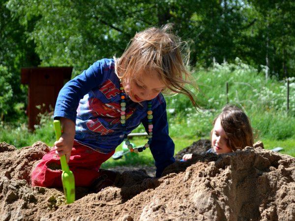 En liten tjej sitter på toppen av en sandhög och gräver.