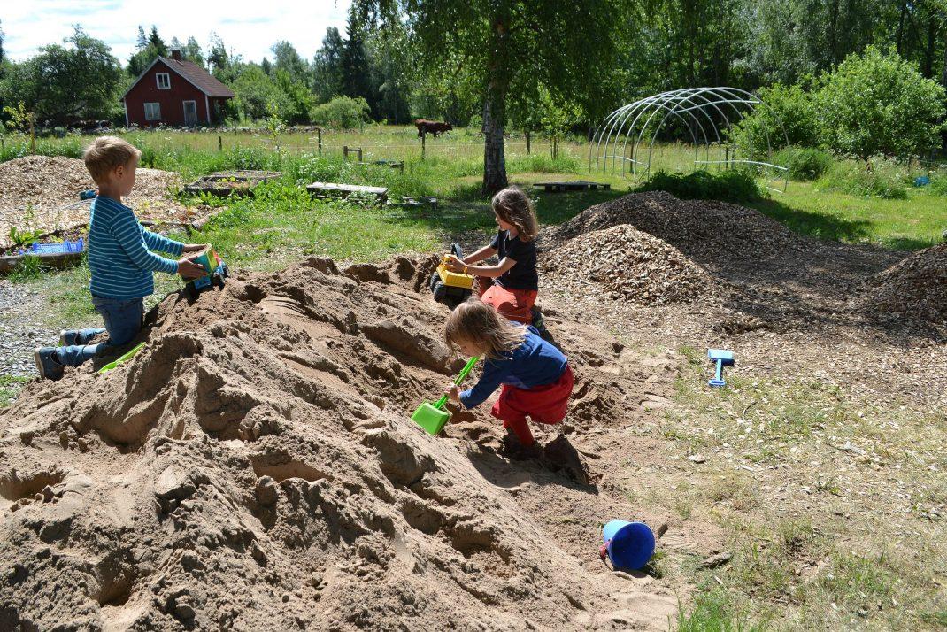 Barn på en hög av sand.