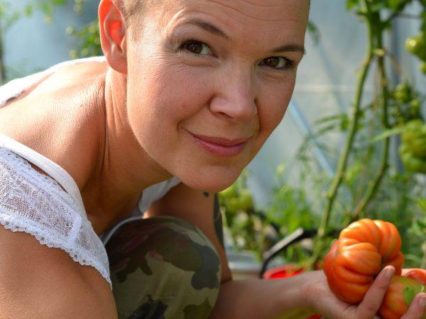 Sara i växthuset med tomater i handen