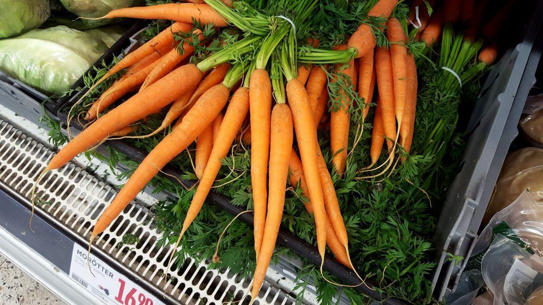 Ett knippe långa morötter i en butikshylla.