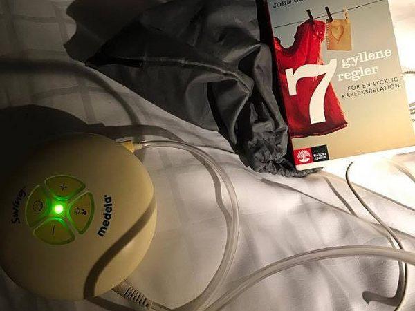 En bröstmjölkpump och bok på en hotellsäng.