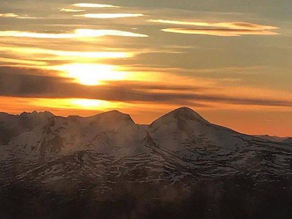 Solnedgång över fjäll, bild tagen från flygplan.
