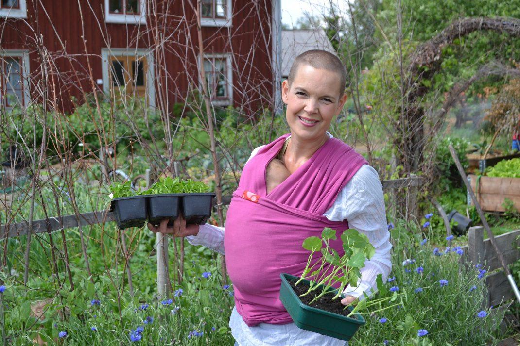Sara bär ett litet barn i sjal och har grönsaksplantor i händerna.