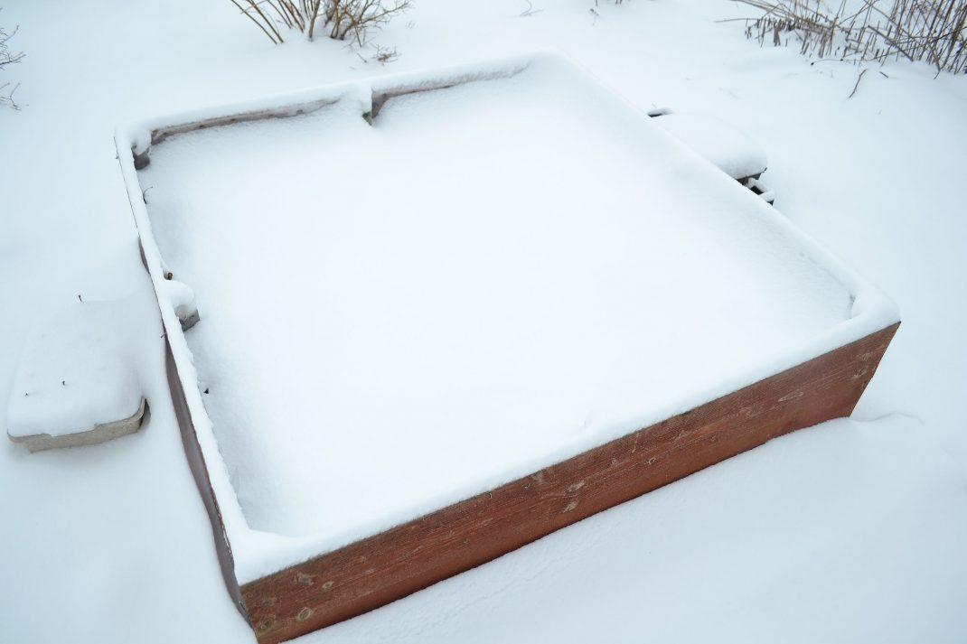 En odlingslåda täckt med snö. March gardening.
