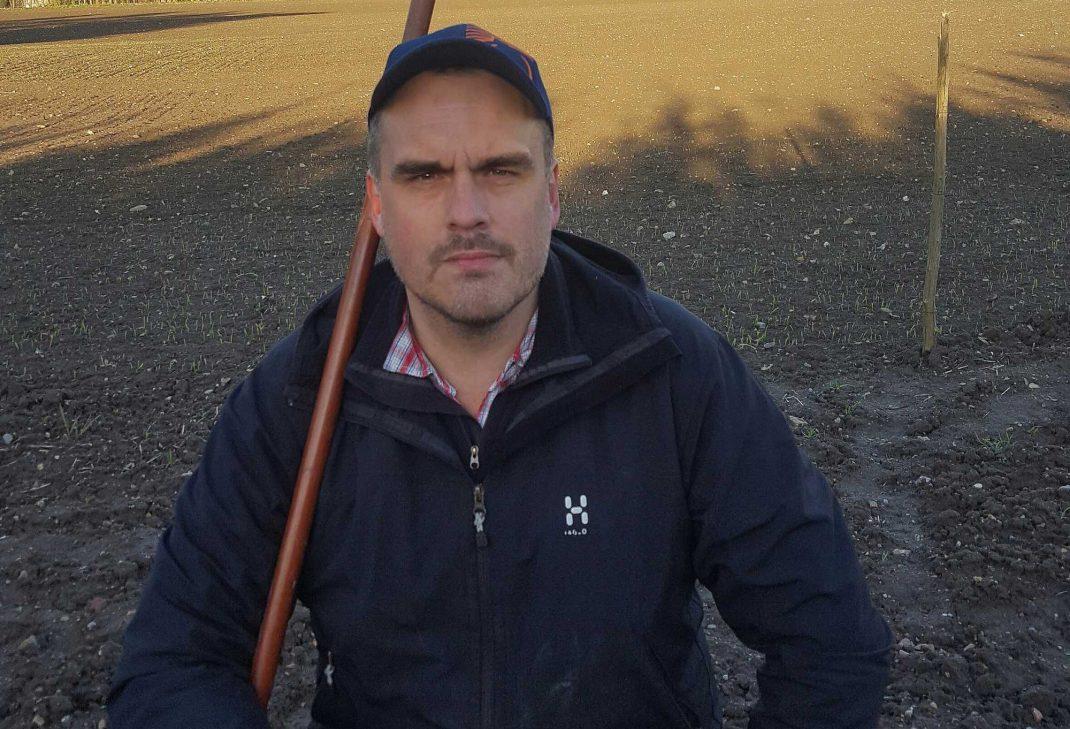 En man sitter framför ett fält av jord.