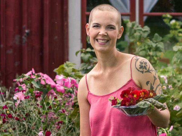 Sara Bäckmo i sin köksträdgård med ett fat sallad i handen.
