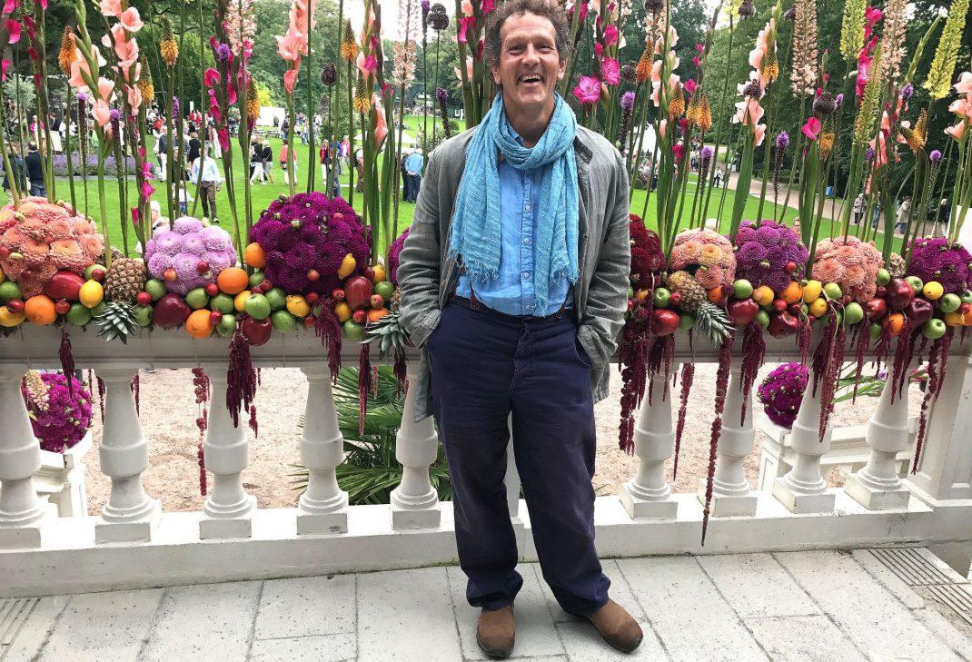Monty Don framför ett blomsterarrangemang på en vit trappa.