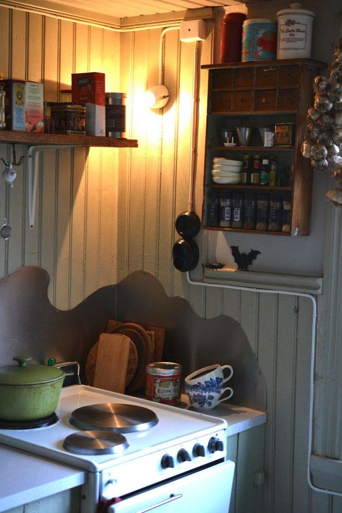 En hörna i köket med spis och kryddhylla.