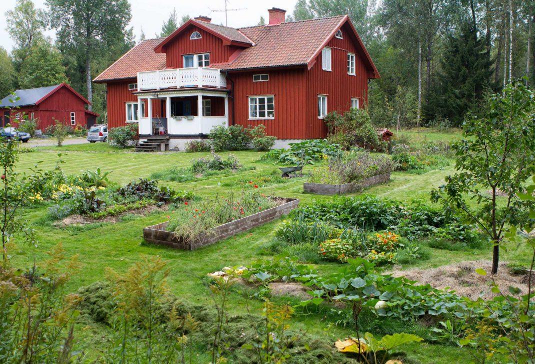 Ett stort rött hus med odlingar i trädgården.