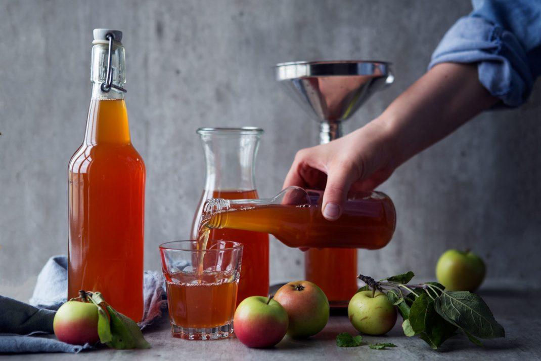 Flaskor och glas fyllda med äppelmust.