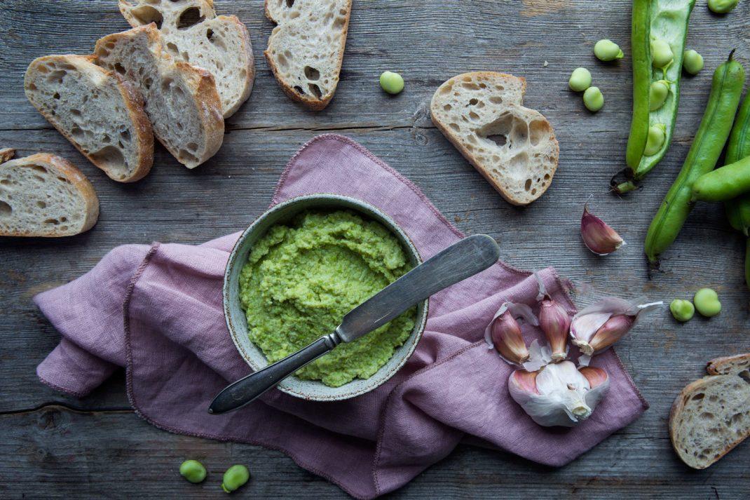 En uppläggning med grön röra av bondbönor och nybakt bröd.