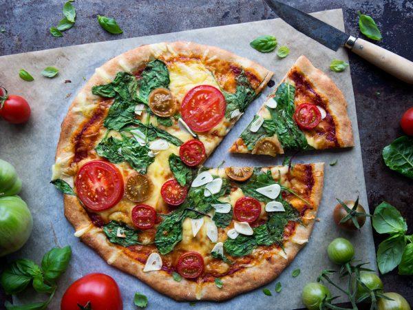 Pizza med spenat, tomat och vitlök.