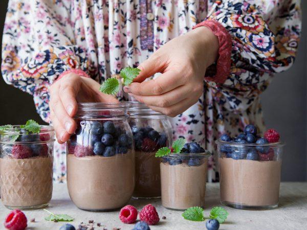 En kvinna dekorerar chokladpudding.