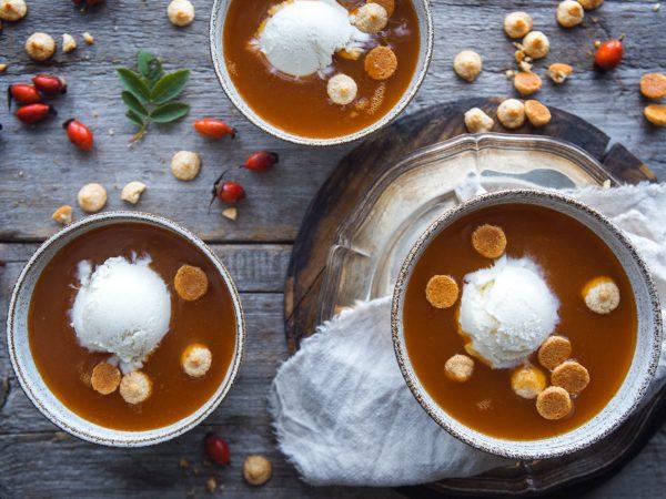Hemgjord nyponsoppa i skål med mandelbeskvier och glass.