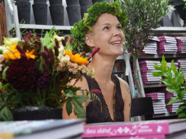 Sara sitter vid ett bord med blommor och tittar uppåt med ett stort leende, iförd eb krans av grönsaker.