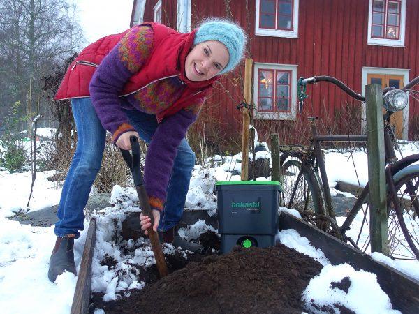 Sara gräver ner bokashi i en odlingslåda.