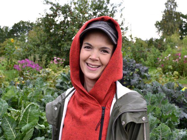 Sara Bäckmo stående i sin köksträdgård, med keps och luvtröja.