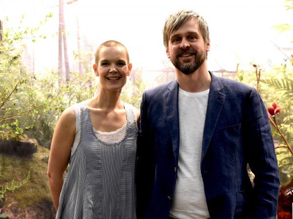 Sara och Johannes står bredvid varandra framför ett ljust växthus och grönska.