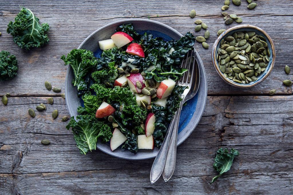 En rund, blå tallrik är fylld av sallad på mörk grönkål och röda äpplen. Den står på ett träbord.