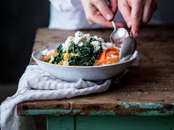 På kanten av ett bord står en tallrik på en handduk. På tallriken ligger en färgglad sallad och två händer tar upp maten med skedar.