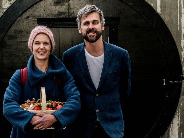 Sara och Johannes står bredvid varandra framför en svartmålad dörr, Sar ha en fruktkorg i famnen.