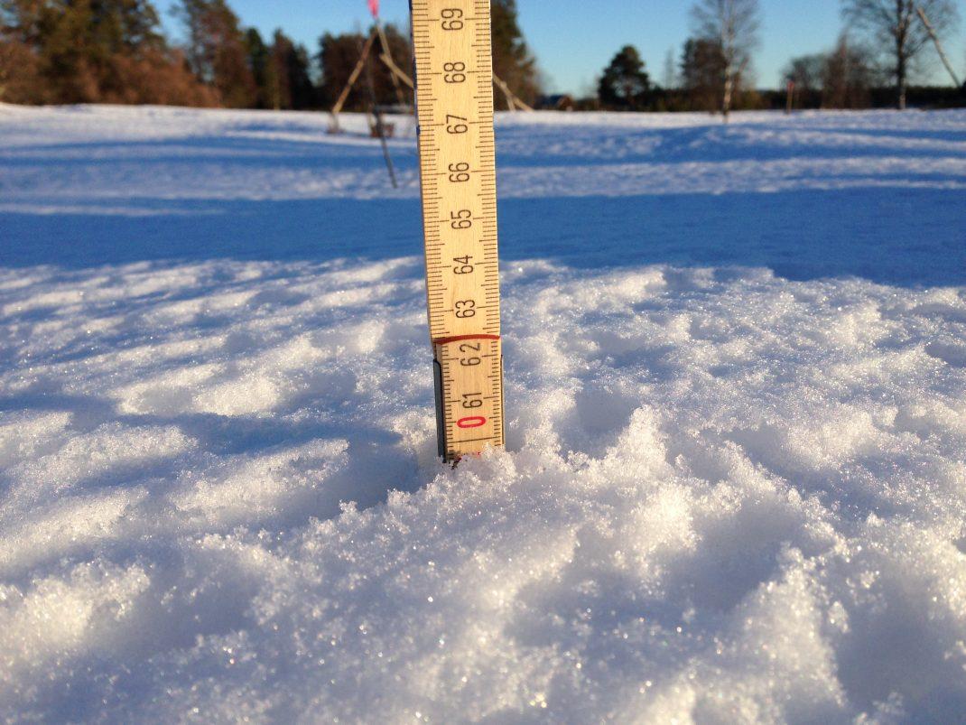 En tumstock är nertryckt i snön och visar ca 60 cm.
