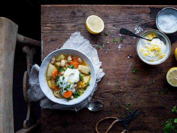 På ett nött träbord står en tallrik med rotsakssoppa, toppad med vit yoghurt, persilja och bönor.