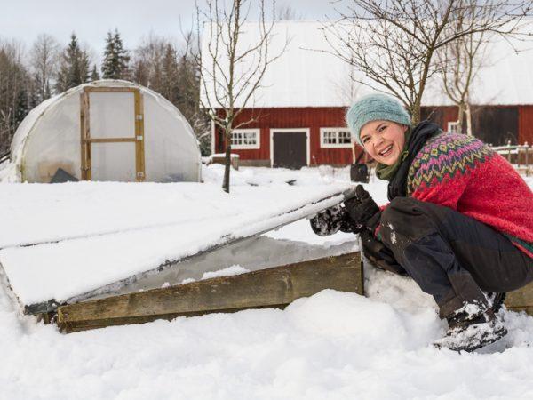 Sara lyfter på locket till en stor odlingslåda. Det är snö i trädgården.