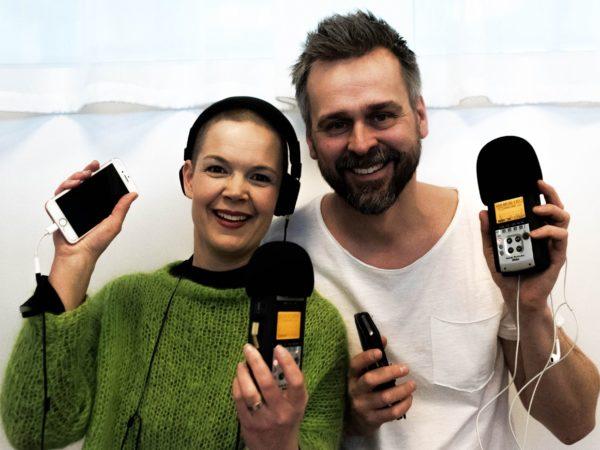 Sara i grön stickad tröja och Johannes i vit t-shirt står bredvid varandra med varsin mikrofon kopplad till sin mobiltelefoner.