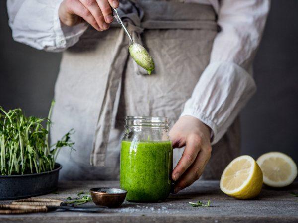 Grön dressing ringlas ner i en glasburk. Bredvid syns citron och salt.
