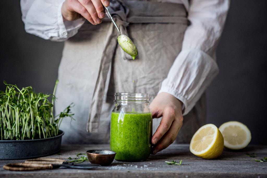 Grön fressing ringlas ner i en glasburk. Bredvid syns citron och salt.