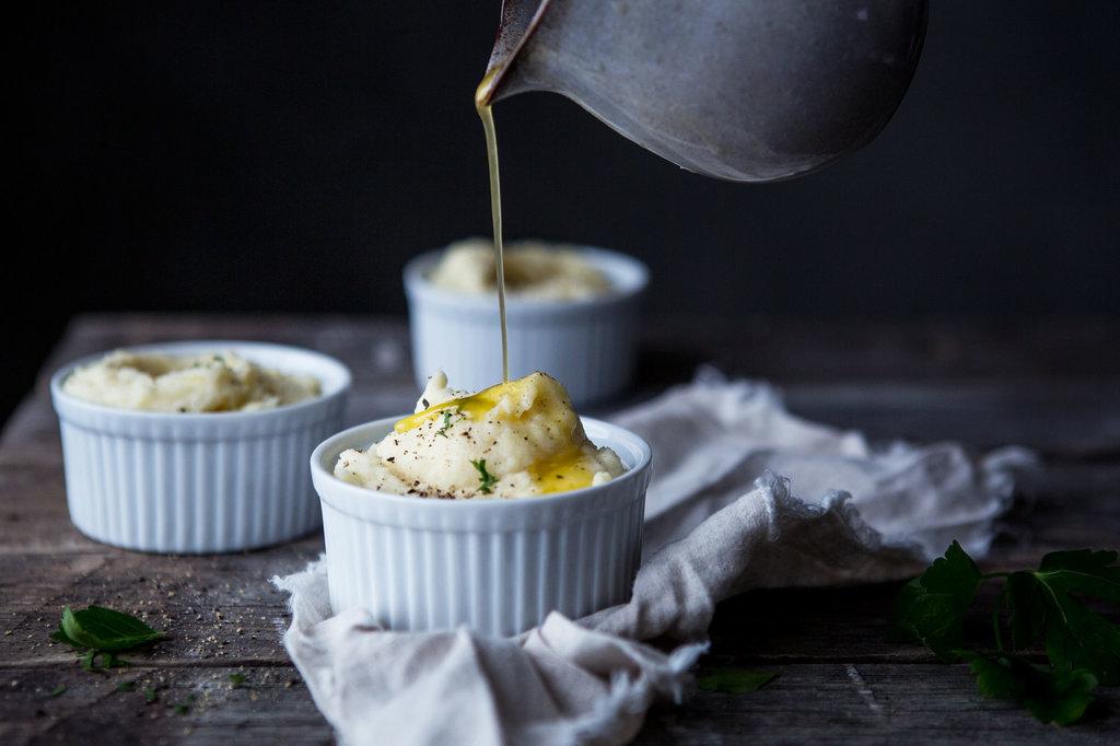 Ljusgult mos är serverat i tre små vita formar. En hand häller över brynt smör i en tunn stråle över den närmsta formen.