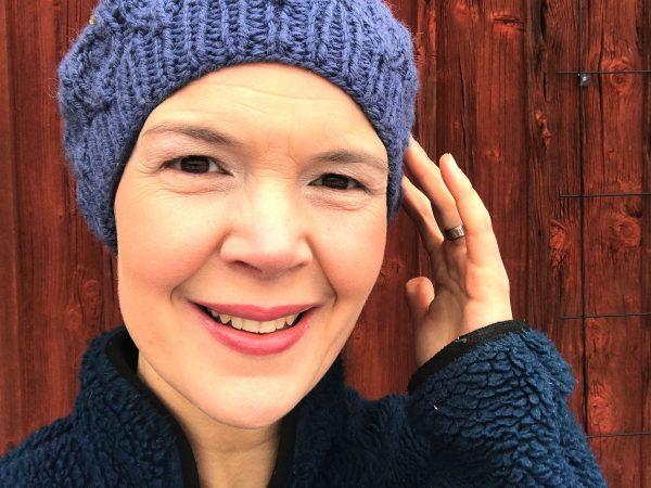 Sara Bäckmo i blå mössa utomhus mot en faluröd vägg.